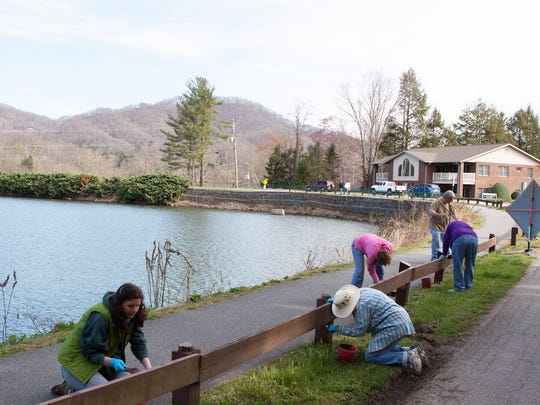 A group of volunteers paints a guardrail along South Lakeshore Drive. The team painted 592 feet of guardrail at Lake Junaluska.