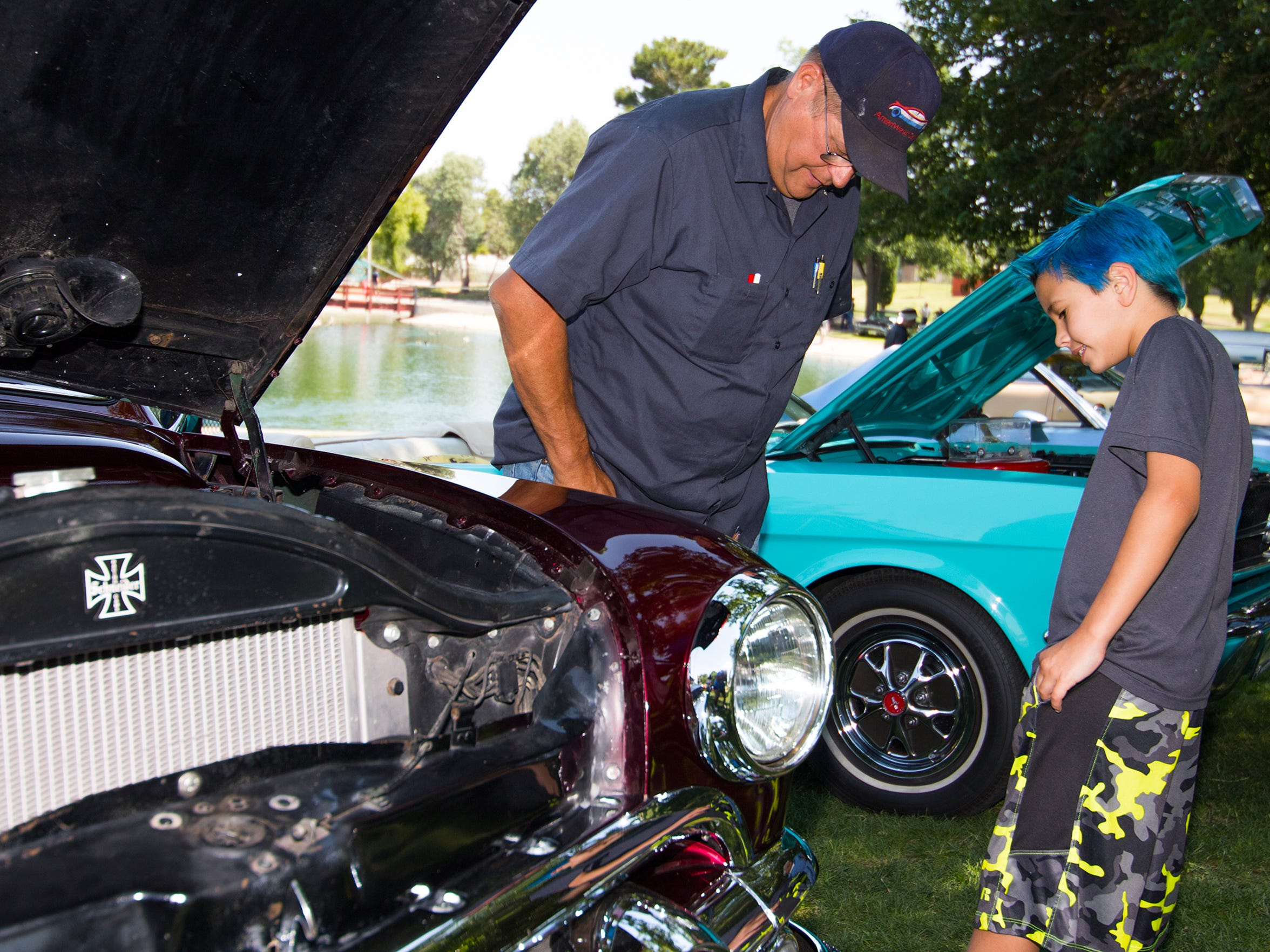 The annual Kars for Kids car show is free to attend. Proceeds from registrations and food benefit Jardín de los Niños. (Pictured) Ted McConaughey and his son Ryan, 10, take a look at the lines of a custom car during the 2016 Kiwanis Kars for Kids Car Show.