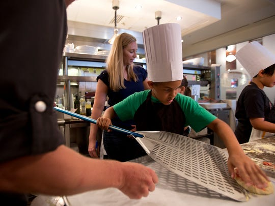 9-year-old Sammy Taylor gets his pizza ready for the oven during a kids cooking class at Sea Salt in Naples on June 25, 2016.