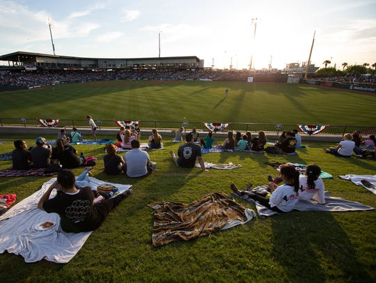 Fans sit on the Left-Field Berm at Whataburger Field