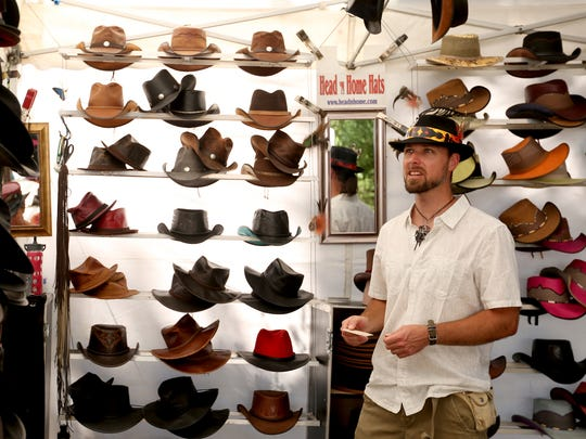 Michael Wilok, of Cottage Grove, and a photographer featured at the Salem Art Fair and Festival, looks over the handmade hat booth of Ronia Grillos, of Freedom, Calif., at Bush's Pasture Park on Friday, July 21, 2017.