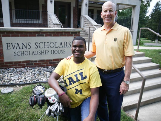 Evans Scholarship recipient Ainslie Woodward, a Cass Tech graduate who will be attending Michigan, and David Robinson, chairman of the Western Golf Association, pose in front of the Evans Scholars House on Friday, July 14, 2017 in Ann Arbor.