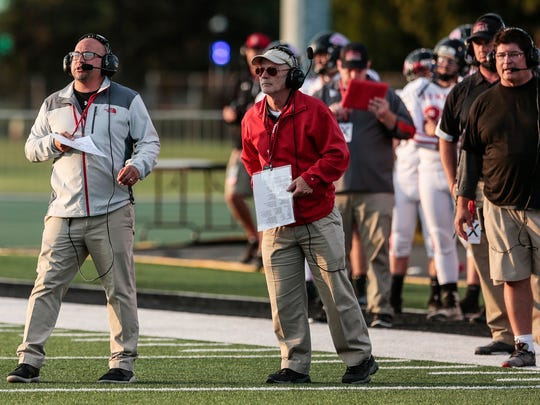 Lowell head coach Noel Dean, left, speaks to players during Prep Kick-off Classic at Wayne State University's Tom Adams Field in Detroit, Friday, August 25, 2017.