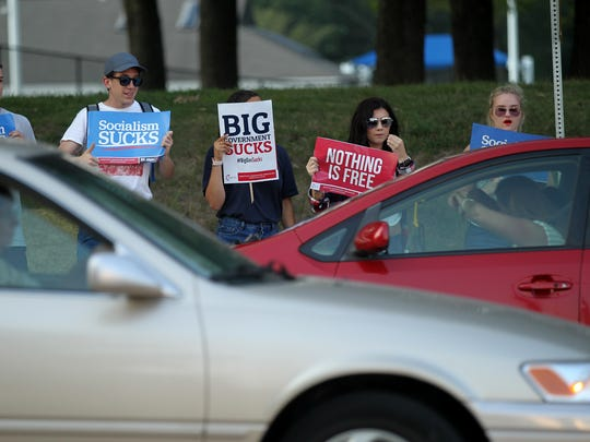 "Protesters react as drivers give them a ""thumbs down"" outside Hancher Auditorium for the arrival of Sen. Bernie Sanders (I-Vt.) on Thursday, Aug. 31, 2017."