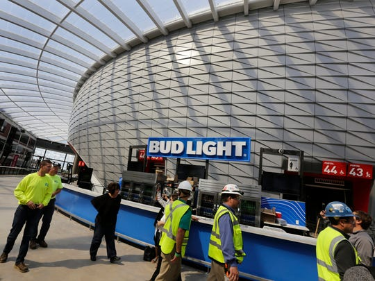 Construction workers walk around the elevated concourse at Little Caesars Arena in Detroit on Wednesday, Sept. 6, 2017.