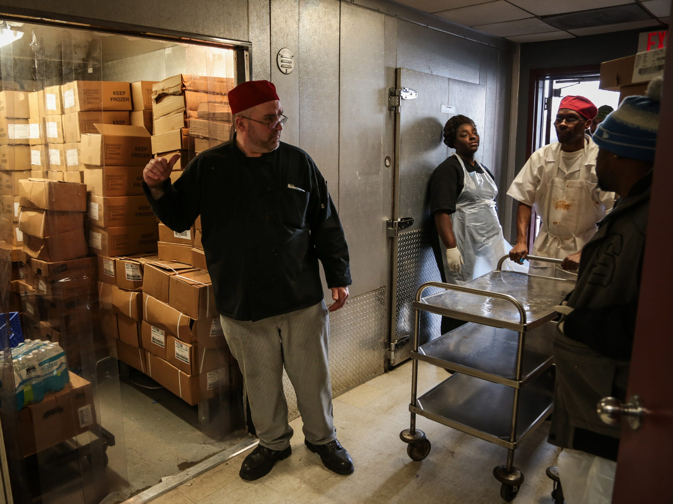 Drew Reeves, 50 of Warren, center, gives instructions to others working in the kitchen at the Salvation Army's Harbor Light Center as he prepares the day's food for the Bed and Bread program's trucks.