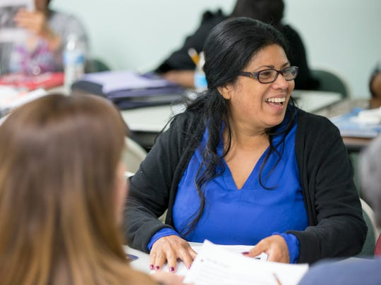 Elsy Mills, originally from Honduras, smiles during a lesson on 19th century America that's part of a series of English culture and language classes held by Neighborhood Christian Legal Clinic and Washington Township Schools, Indianapolis, Friday, 22, 2017.
