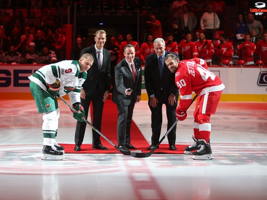 Red Wings' Henrik Zetterberg and the Minnesota Wild's Mikko Koivu accompany Chris Ilitch, center, Nicklas Lidström, left, and Mickey Redmond for the ceremonial puck drop in the Little Caesars Arena regular-season opener in Detroit on Thursday, Oct. 5, 2017.