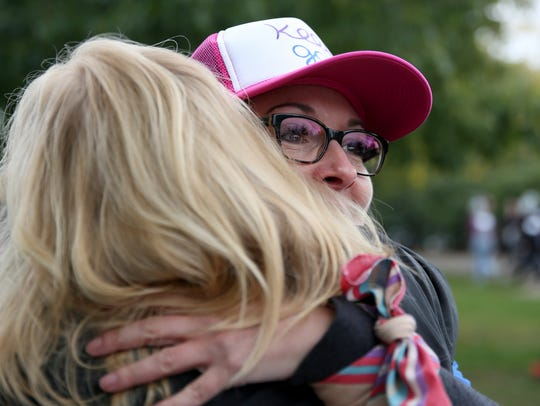 Kim Kinney, facing, of Salem, hugs Shawn Lott, the