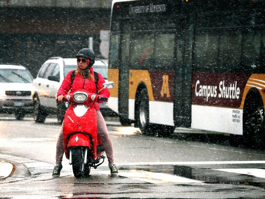 A commuter braves the first snow of the season on a