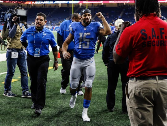 Golden Tate celebrates as he walks off the field after