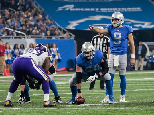 Lions QB Matthew Stafford talks to teammates as center Travis Swanson looks on against the Vikings at Ford Field last season.