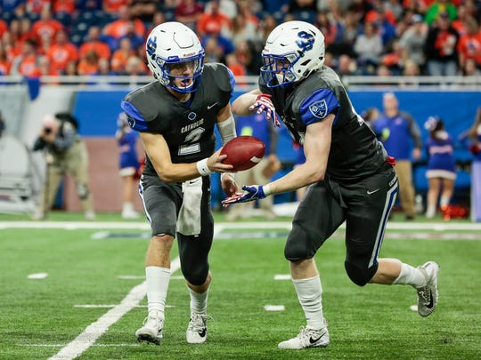 Grand Rapids Catholic Central quarterback Jack Bowen (2) passes the ball to running back Nolan Fugate (24) during the first half of the Division 4 championship game on Friday, Nov. 24, 2017, at Ford Field.