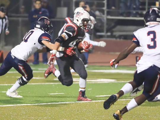 Tulare Western's David Alcantar (C)  (43) rushes against San Joaquin Memorial during the Central Section Division II Championship high school football game Bob Mathias Stadium on Dec 1, 2017.