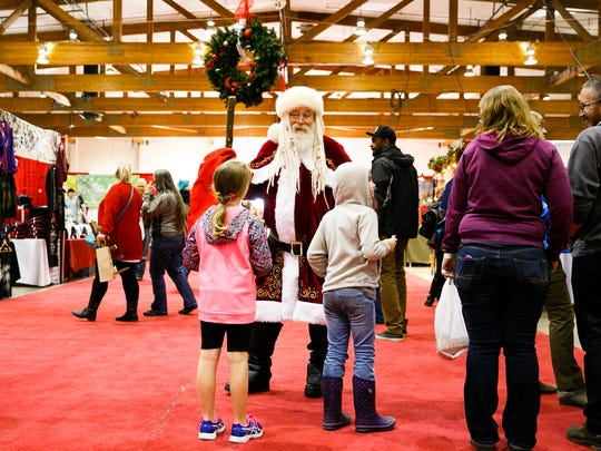 Santa Claus talks to children at the 18th annual Salem Holiday Market on Saturday, Dec. 9, 2017, at the Oregon State Fairgrounds.