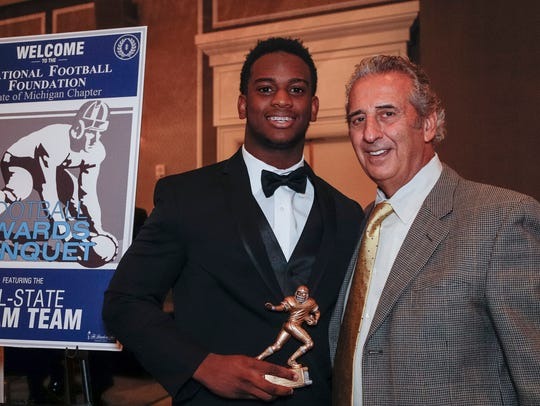 Detroit Free Press 2017 All-State Dream Team member Marcel Lewis of Clinton Township Chippewa Valley poses for a photo with N.F.F. State of Michigan Chapter president Tony Versaci at the Dearborn Inn, Dec. 10, 2017.