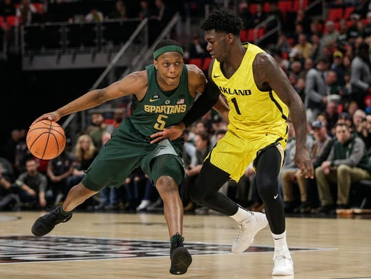 MSU's Cassius Winston dribbles against Oakland's Kendrick Nunn in the first half at Little Caesars Arena on Dec. 16, 2017.