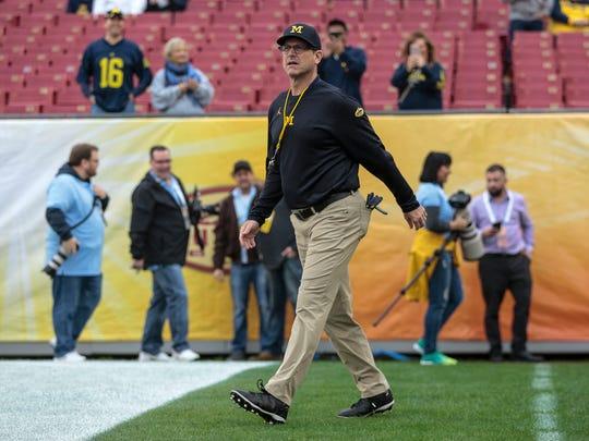 Michigan Wolverines head coach Jim Harbaugh enters