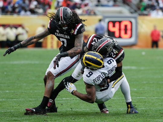 Donovan Peoples-Jones is tackled by South Carolina defensive backs D.J. Smith (24) and JaMarcus King during the second half of the Outback Bowl on Monday.