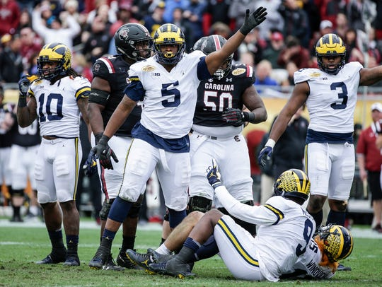 Michigan defensive lineman Aubrey Solomon (5) celebrates a South Carolina fumble in the Outback Bowl.