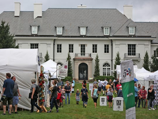 Art lovers roam the grounds next to the Lilly House