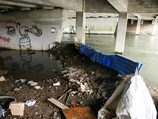 Homeless campers built a dam to keep their items dry while they stayed under the Highway 22 overpass that crosses Mill Creek near Costco and Lowe's. They made the structure using dirt, wooden pallets, tarps and makeshift sandbags made with Walmart shopping bags.