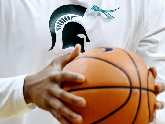 Michigan State's Nick Ward wears a teal ribbon, the