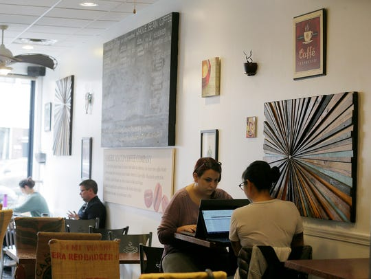 Lauren Kloza of Asbury Park and Kelsey Kloza of Ocean Grove, sisters, work on their laptops at America's Cup Coffee Co. in Asbury Park, NJ Friday February 16, 2018. Verizon will offer free Wi-Fi to businesses, residents and others along Cookman and Springwood avenues in exchange for installing the nodes - mini cell towers - for a 5G cellular network.