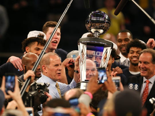 John Beilein raises the trophy after winning the Big Ten tournament championship game, 75-66, over Purdue on March 4, 2018 at Madison Square Garden in New York.