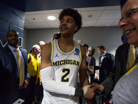 Jordan Poole is greeted by coaches and staff in the