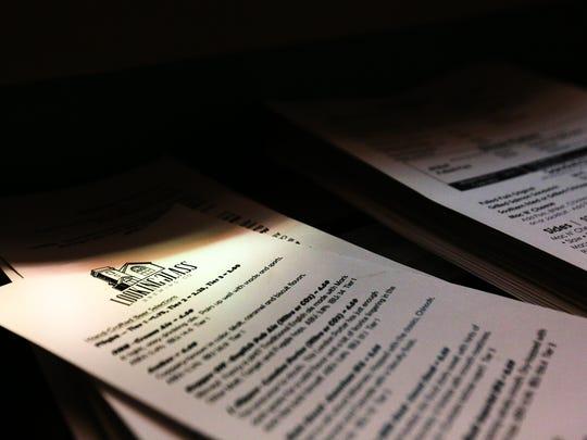 Beer and food menus sit in stacks next to the hosting