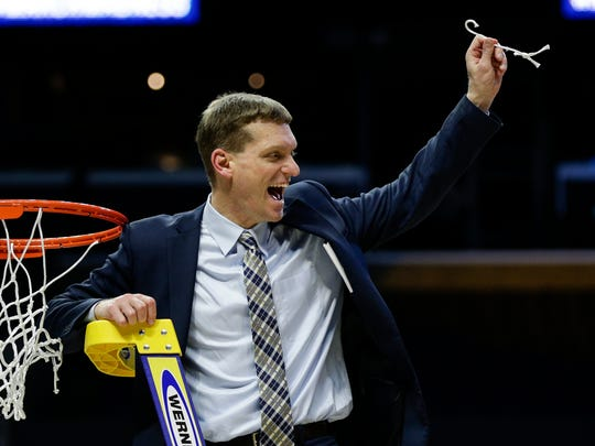 Michigan assistant coach Luke Yaklich celebrates with a piece of the net at Staples Center in Los Angeles, after defeating Florida State in the Elite Eight on Saturday, March 24, 2018.