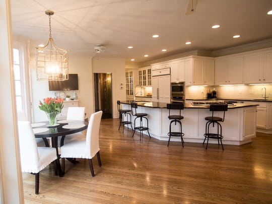 The kitchen and breakfast room are clean-lined and  contemporary with room for a crowd to gather. The wall at left is a long stretch of mullioned glass.