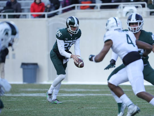 Michigan State punter Jake Hartbarger kicks during