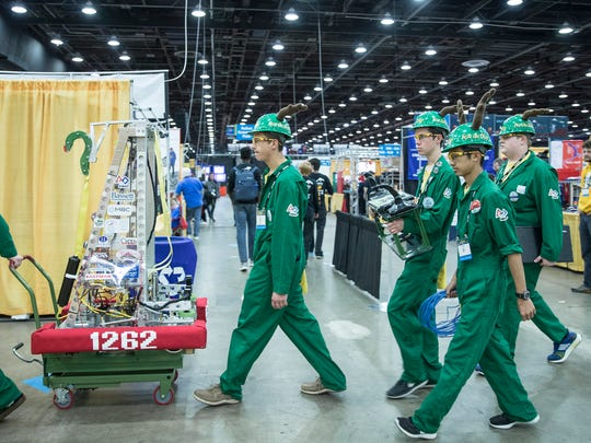 Team Stags walk through the pit with their robot on