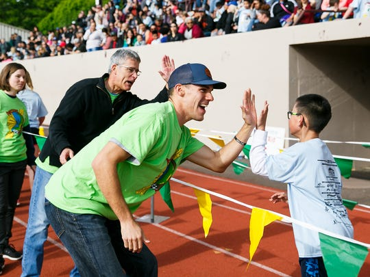 Davis, center, and Bob Jones, left, congratulate runners as they finish the 36th annual Awesome 3000 on Saturday, May 5, 2018, at McCulloch Stadium in Salem, Ore.