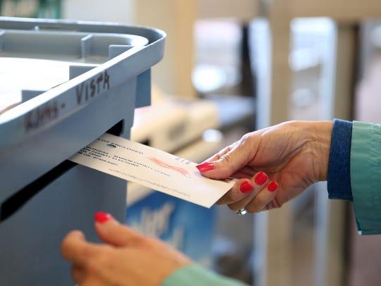 Carol Montgomery, 66, of Salem, drops off a ballot