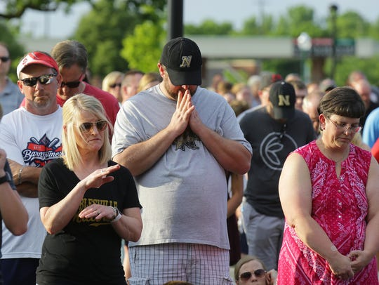 Community members pray together during a prayer vigil