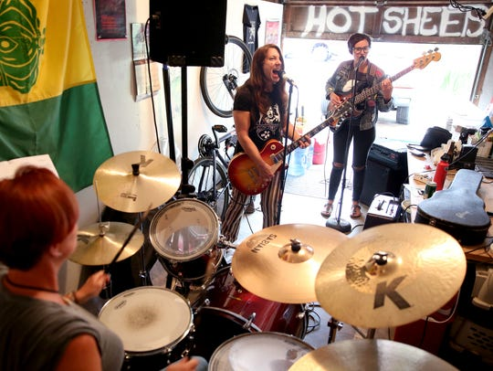 Hot Sheets, made up of guitarist Karen McFarlane Holman, center, drummer Jamie Sloan, left, and bassist Jessica Amos rehearses at Sloan's home in Salem on Friday, June 8, 2018.