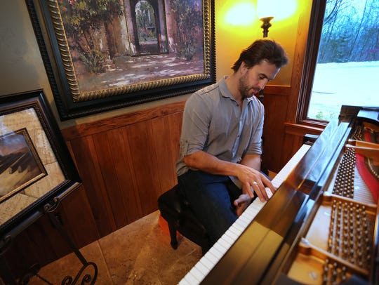 Ben Utecht plays a few keys on the piano, in his Lakeville,