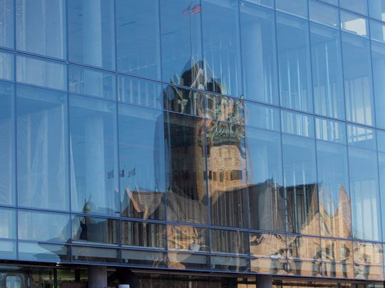 The Johnson County Courthouse is seen reflected against the windows of the MidWestOne building on South Clinton Street in Iowa City.