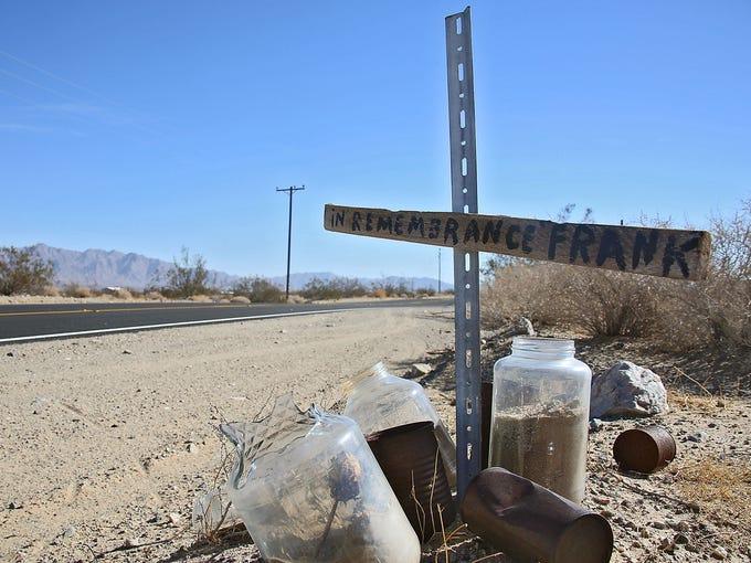 """A roadside cross reads """"In Remembrance Frank"""" along"""