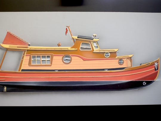 Airbrush artist Kerry Elwood of Salem shows off the rendering of the hand-crafted wooden houseboat that he's been commissioned to build.