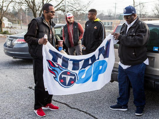 Ray Jones (right), Angelo Blackson's brother-in-law, unfurls a Titans flag as he waits with family and friends to board a bus to watch Blackson play the New York Jets on Sunday morning.