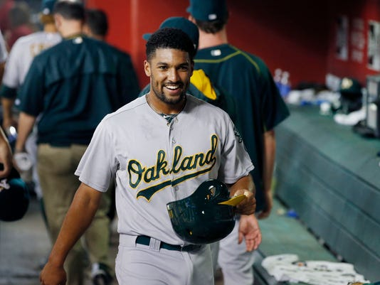 Oakland Athletics' Marcus Semien smiles in the dugout after scoring a run against the Arizona Diamondbacks during the third inning of a baseball game Friday, Aug. 28, 2015, in Phoenix. (AP Photo/Ross D. Franklin)