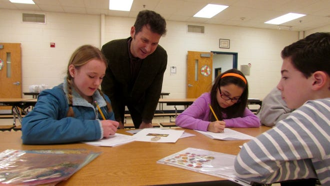 Artist Neil Patterson (second from left) is overseeing the creation of a mural at Marlton Elementary School in the school's cafeteria. All of the students at the school will help create the fruit-themed mural.