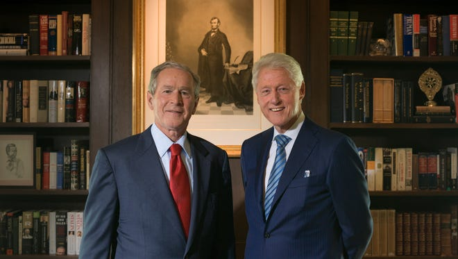 George W. Bush and Bill Clinton stand near a rendering of President Lincoln in Bush's office at the George W. Bush Presidential Library and Museum on the SMU campus in Dallas.
