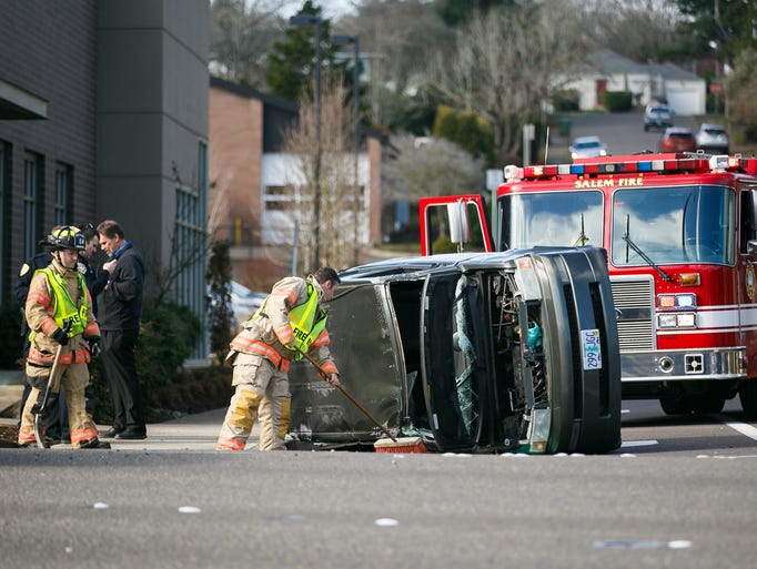 Salem firefighters sweep up glass from a traffic collision