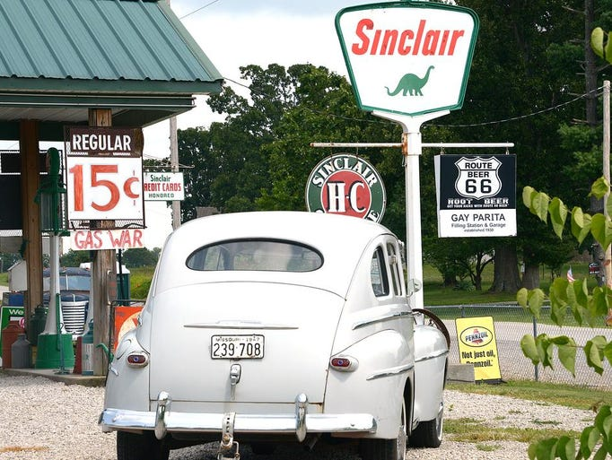 "An old Ford sits in the restored Gay Parita Sinclair gas station on Route 66 in Paris Springs. A ""gas war"" sign is showing the price per gallon to be a mere 15 cents."