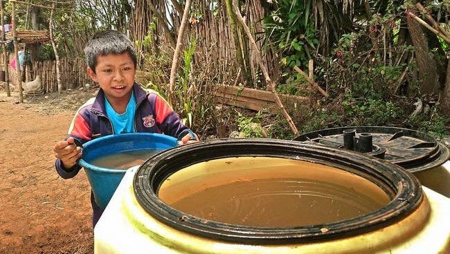 A boy stands near a water container in a Guatemalan village.